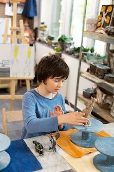 Getalenteerde schooljongen die figuren in klei beeldhouwen op de kunstacademie