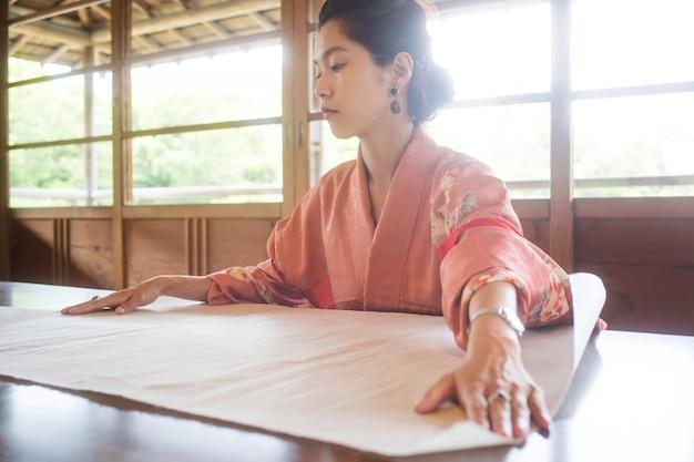 Getalenteerde vrouw die met japans papier werkt