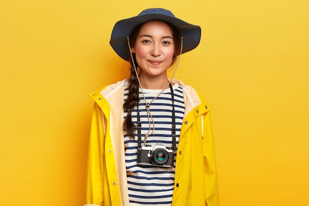 Getalenteerde vrouwelijke fotograaf maakt professionele foto's tijdens avontuurlijke reis, gebruikt retro camera, draagt stijlvolle hoed, gele regenjas, geniet van vakantie
