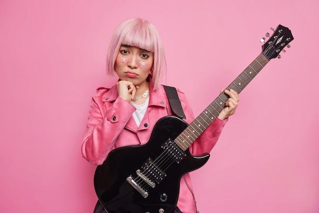 Getalenteerde vrouwelijke gitarist kijkt verdrietig, speelt zwarte elektrische gitaar houdt niet van haar nieuwe nummer overstuur niemand luistert haar band draagt jas
