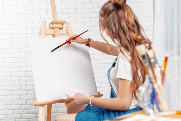 Getalenteerde vrouwelijke schilder die op schildersezel schildert