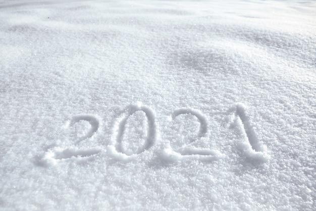 Getallen, kalenderdatum, inscriptie 2021 op natuurlijke besneeuwde ondergrond in de winter