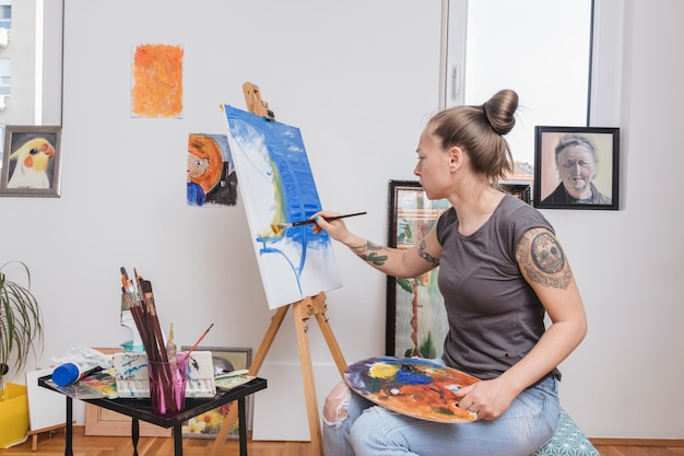 Getatoeã «rde jonge vrouw die in blauw op canvas schildert