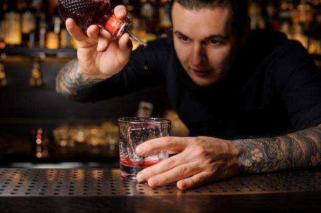 Getatoeëerde barman die een bittertje toevoegt aan de heerlijke cocktail uit de speciale dasherfles op de toog