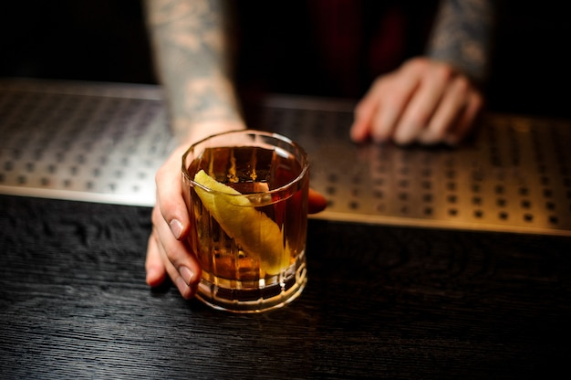 Getatoeëerde barman serveert een glas rusty nail-cocktail met sinaasappelschil op de toog