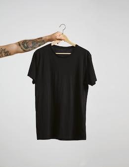 Getatoeëerde biker hand houdt hangen met lege zwarte t-shirt van premium dun katoen, geïsoleerd op wit
