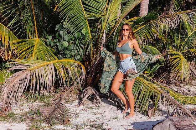 Getatoeëerde blanke vrouw in denim shorts en groene trendy crop top op het strand