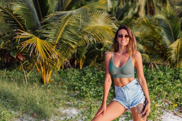 Getatoeëerde blanke vrouw in denim shorts en groene trendy crop top