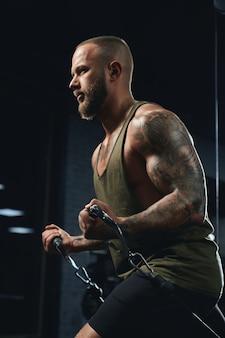 Getatoeëerde bodybuilder die lage kabelovergangsoefening doet.