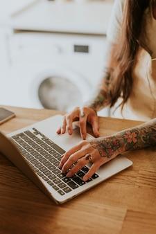 Getatoeëerde eigenaar van een klein bedrijf werkt op haar laptop