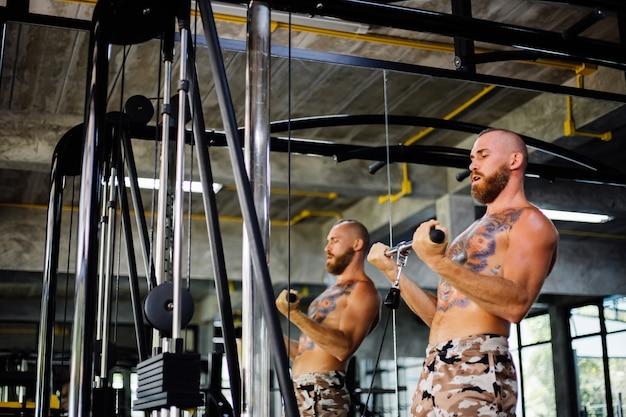 Getatoeëerde fit man doen oefening in de sportschool