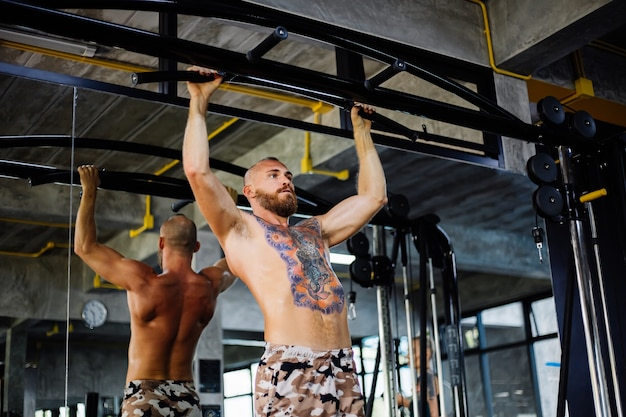 Getatoeëerde fit man doet oefeningen in de sportschool