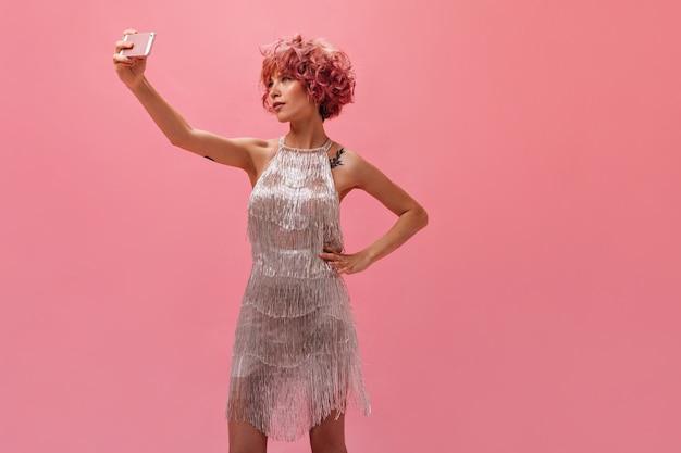 Getatoeëerde gebruinde vrouw in zilveren jurk maakt selfie op roze muur