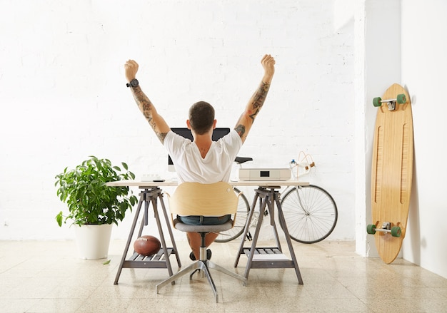 Getatoeëerde gelukkige freelancer voor zijn werkruimte, omringd door zijn hobby speelgoed longboard, vintage fiets en groene plant, terwijl hij zijn hand in de lucht strekt terwijl hij pauze neemt