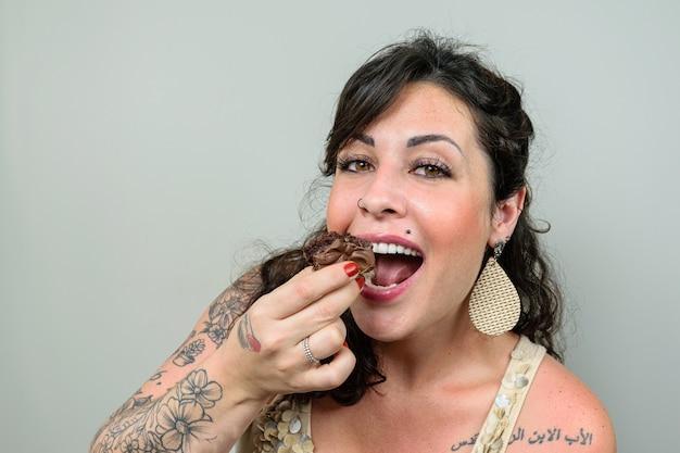 Getatoeëerde, glimlachende vrouw met open mond, klaar om een braziliaanse honingcake te verslinden.