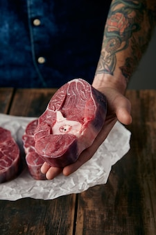 Getatoeëerde hand biedt een stuk vleesstok aan boven twee steaks op ambachtelijk papier, close-up