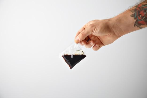 Getatoeëerde hand houdt klein pakket met sojasaus voor noedels wokpasta