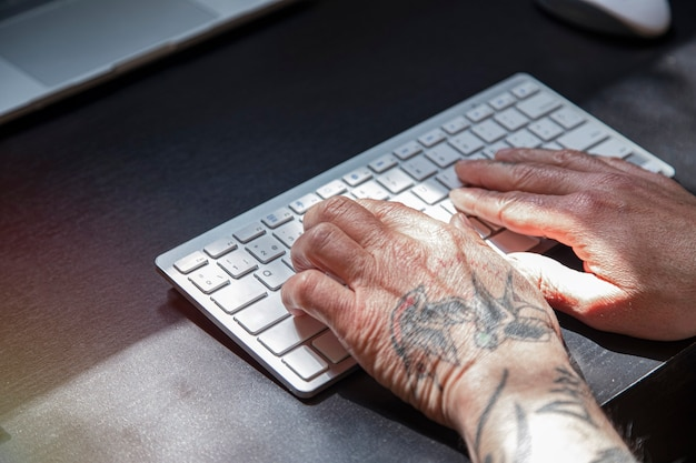 Getatoeëerde handen die aan laptop werken