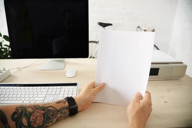 Getatoeëerde handen houden een pak blanco vellen papier vast voordat ze in de lade van de thuisprinter op het werkende bureaublad worden geladen