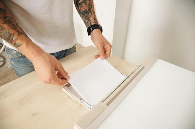 Getatoeëerde handen laden mft-apparaat thuis op met een nieuw pak vellen papier