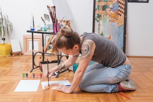 Getatoeëerde jonge vrouw zittend op de vloer en schilderen