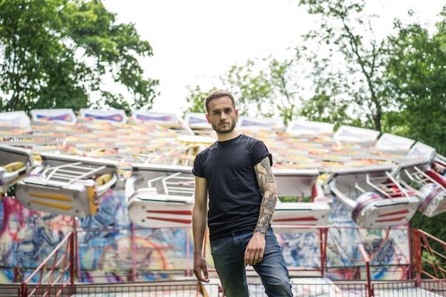 Getatoeëerde jongeman in een pretpark op de achtergrond van een draaimolen