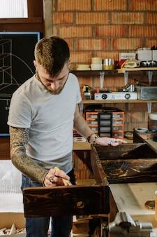 Getatoeeerde kunstenaar die vernisverf op houten meubilair toepast op ambachtworkshop