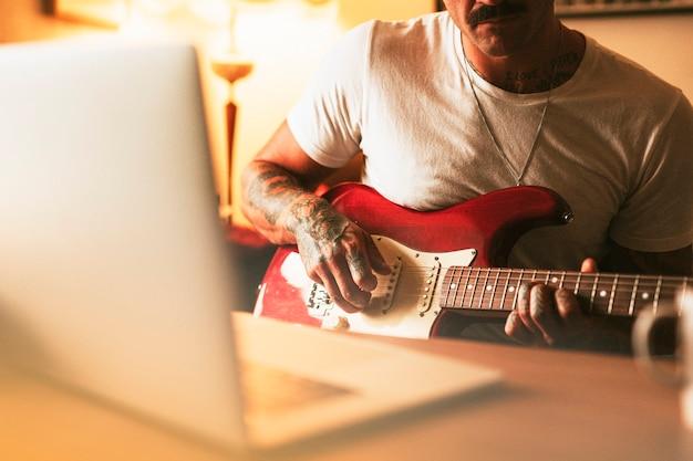 Getatoeëerde man die thuis elektrische gitaar beoefent