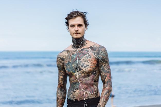 Getatoeëerde man met een koptelefoon tegen de blauwe lucht op de oceaan