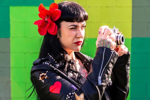 Getatoeëerde rocker vrouw in leren jas, en bloem in haar op groene muur een foto maken met een vintage camera.