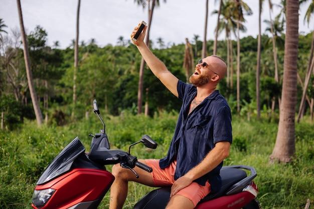 Getatoeëerde sterke man op tropische jungle veld met rode motor