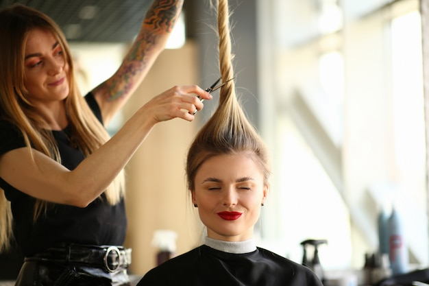 Getatoeëerde stylist knippen haar van gesloten ogen vrouw