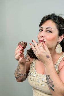 Getatoeëerde vrouw die een klein stukje braziliaanse honingcake eet en bijna lacht.