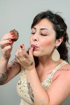 Getatoeëerde vrouw likt haar vinger en trekt een gezicht van voldoening voor het eten van een stuk braziliaanse honingcake.