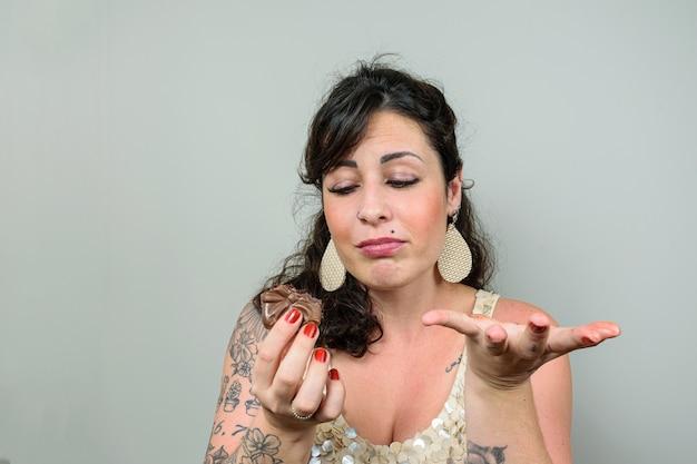 Getatoeëerde vrouw met een gezicht van spijt omdat ze braziliaanse honingcake heeft gegeten.
