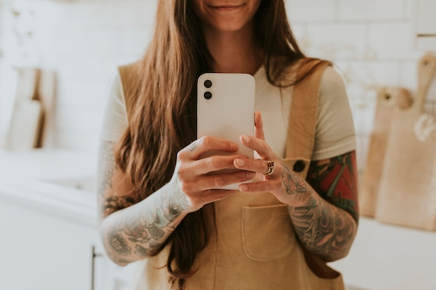 Getatoeëerde vrouw smartphone in een lichte keuken
