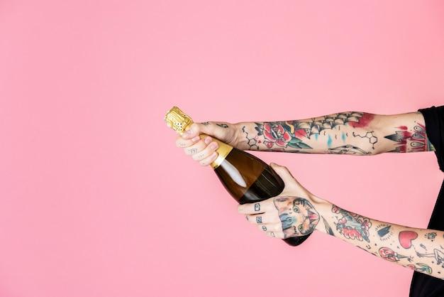 Getatoeëerde vrouwelijke hand met een fles champagne