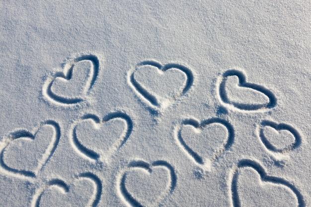 Getekend in het winterseizoen, het hart op de sneeuw, de natuur na sneeuwval en op het oppervlak van de sneeuw, het hart is getekend als een symbool van liefde