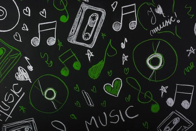 Getekende muzieknoten met cassette; compact disc op blackboard