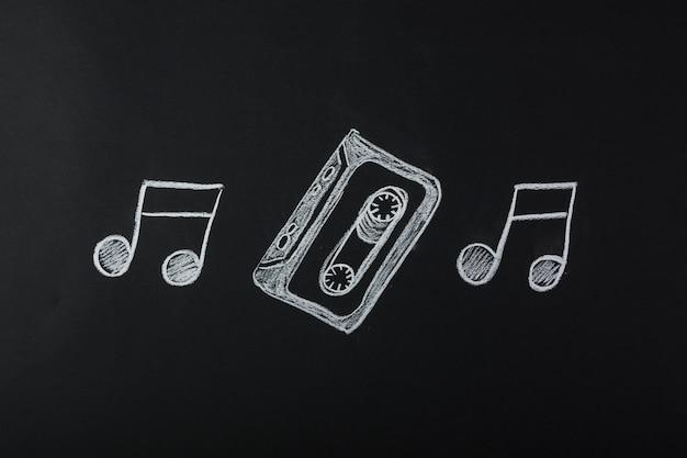 Getekende muzieknoten met cassette tape op blackboard