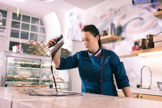 Getempereerde chocolade. ervaren vrouwelijke chocolatier die een blauw jasje draagt en geweldige getempereerde chocolade kookt