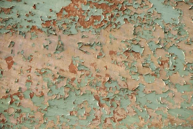 Getextureerde muur met kleurrijke verf, delen die van ouderdom af vlokken vallen.