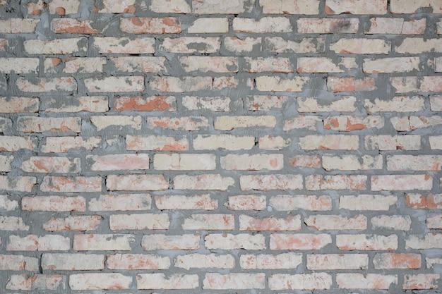 Getextureerde rode bakstenen en cementmuur