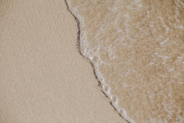 Getij met bellen die op zand lopen