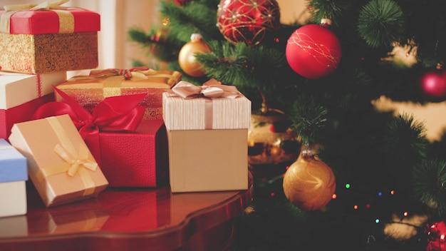 Getinte 4k-beelden van kerstboom en veel dozen met geschenken en cadeautjes 's ochtends in de woonkamer