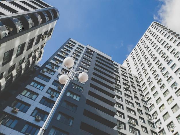 Getinte afbeelding van een hoog modern woongebouw gemaakt van beton en glas tegen blauwe lucht op een zonnige dag