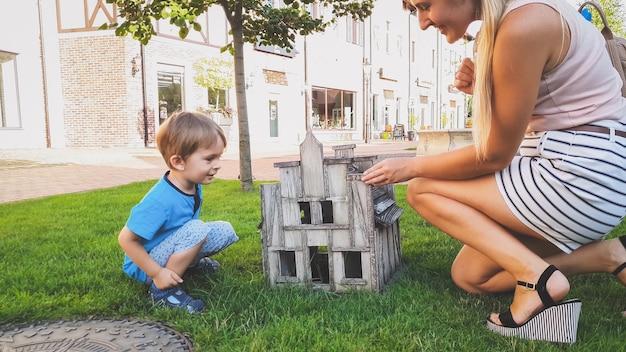 Getinte afbeelding van een lachende kleine jongen die met een jonge moeder in het park zit en naar binnen kijkt in een klein houten huis