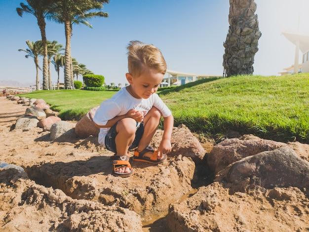 Getinte afbeelding van een schattige peuterjongen die op het zandstrand zit en een kasteel bouwt van nat zand