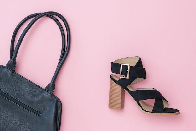 Getinte afbeelding van een zwarte damesschoen en een zwarte tas op een roze achtergrond. mode damesaccessoires.