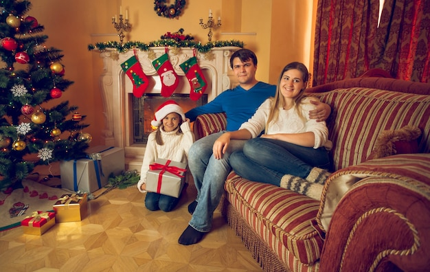 Getinte afbeelding van gelukkig gezin met dochter zittend op de bank in de woonkamer ingericht voor kerstmis
